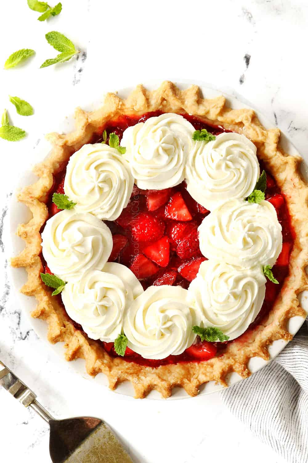 top view of fresh strawberry pie garnished with dollops of whipped cream