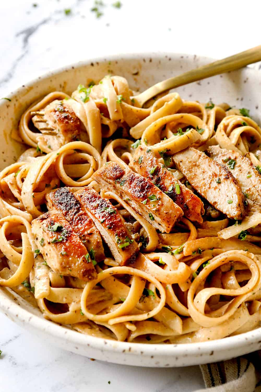 showing how to serve chicken alfredo pasta by slicing chicken and adding to a bowl of fettuccine Alfredo