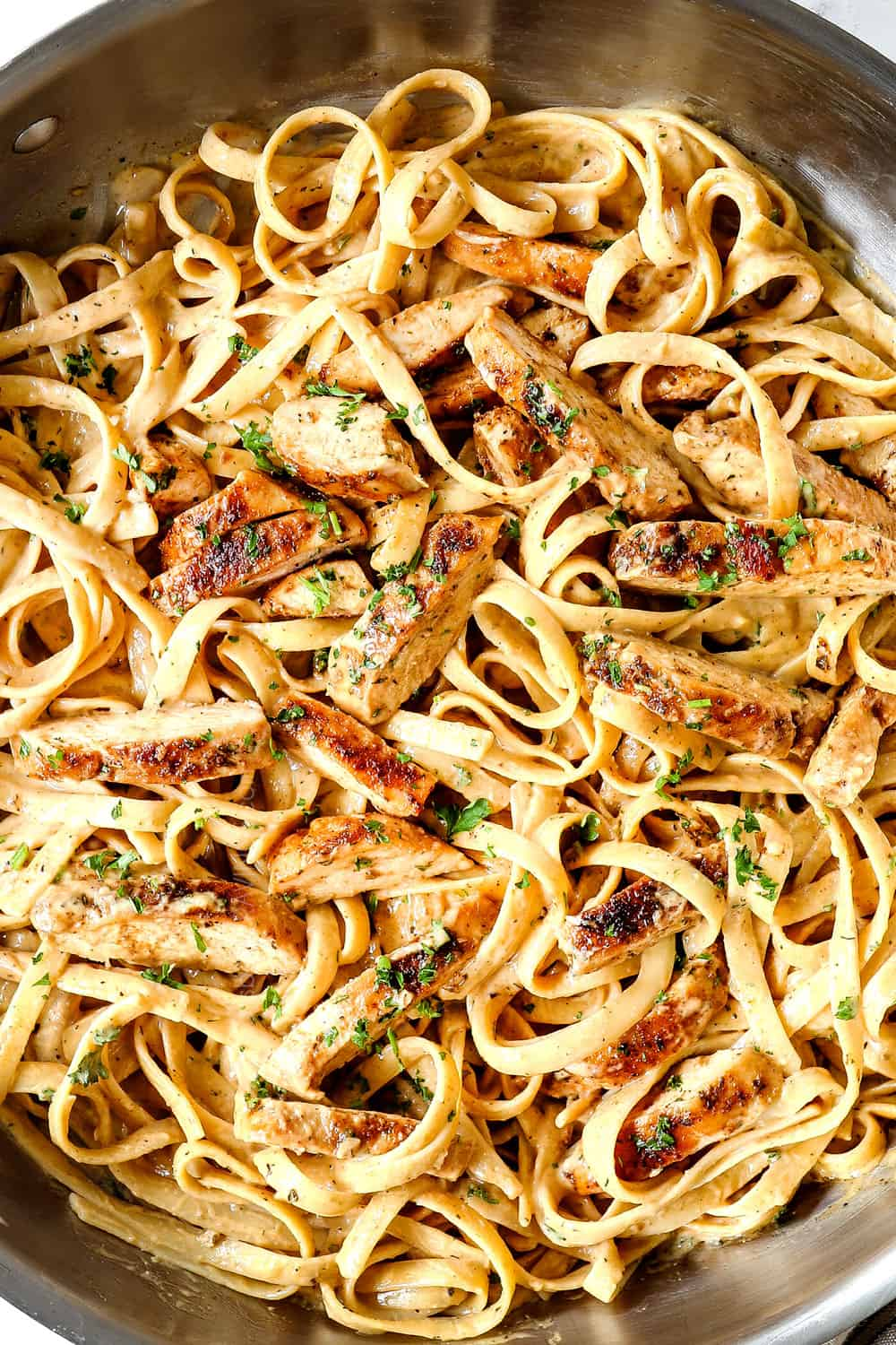 showing how to make Chicken Alfredo pasta by tossing the blackened chicken with the fettuccine pasta