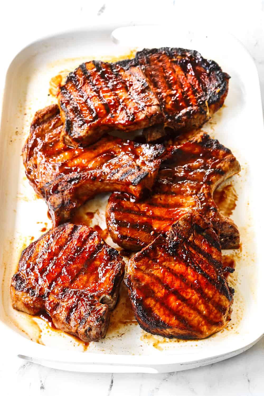 grilled bone in pork chops on a white platter