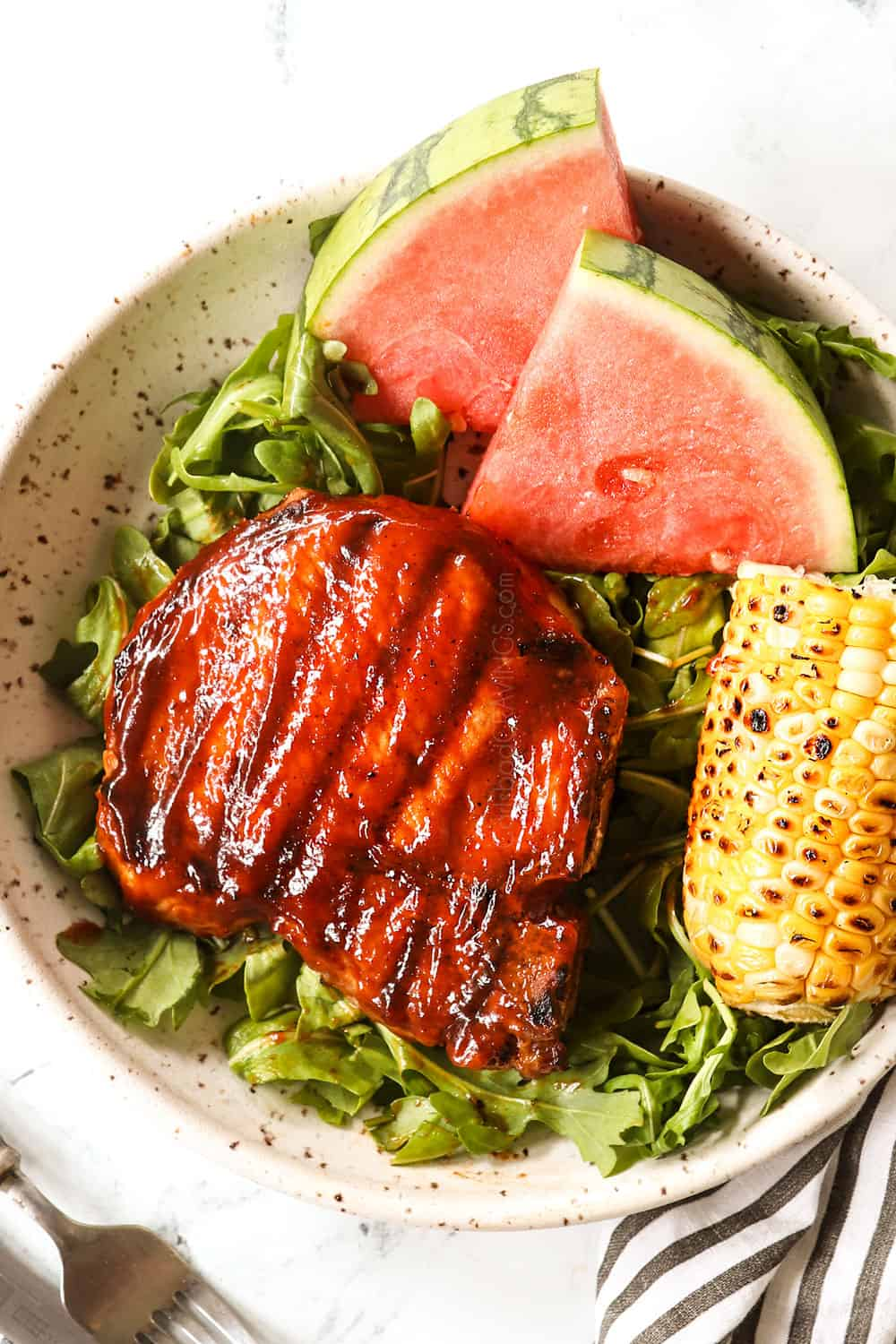 grilled bone in pork chops on a plate with salad, watermelon and grilled corn on the cob