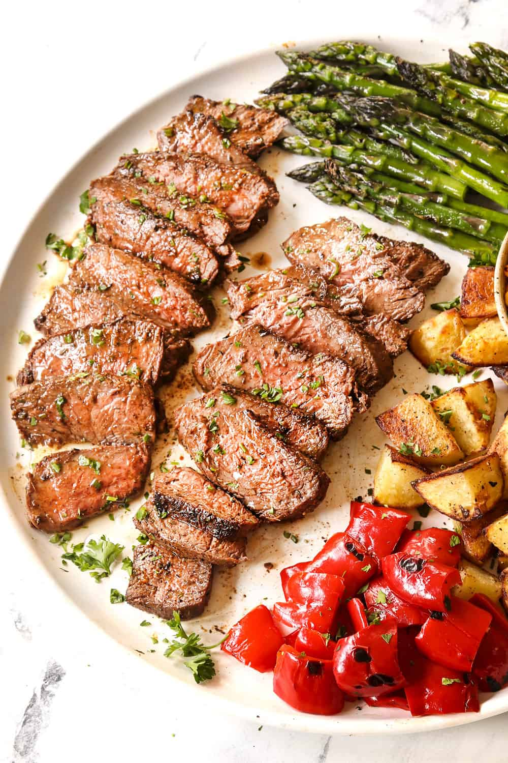 top view of sliced grilled sirloin steak on a white platter