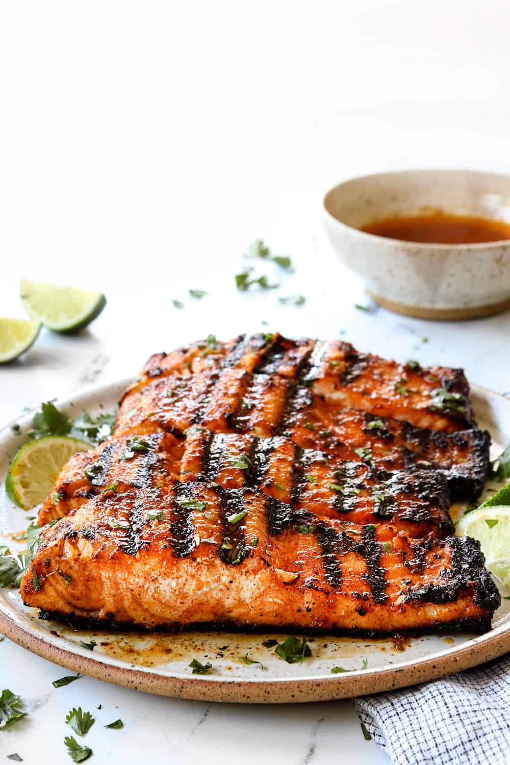grilled salmon recipe on a plate garnished by cilantro