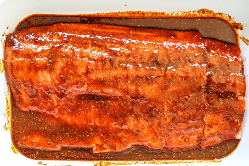 showing how to grill salmon by marinating salmon in a marinade in a 9x13 dish