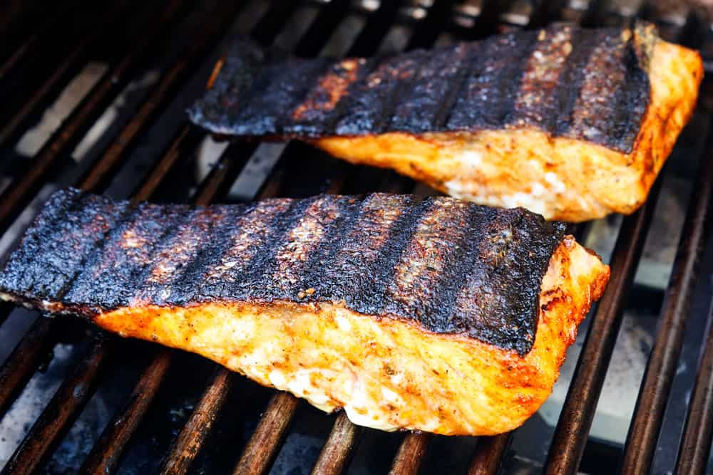showing how to grill salmon by flipping salmon over so it's skin side up