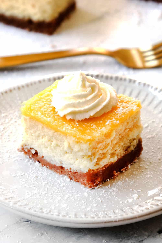 lemon cheesecake bar on a white plate dusted powdered sugar
