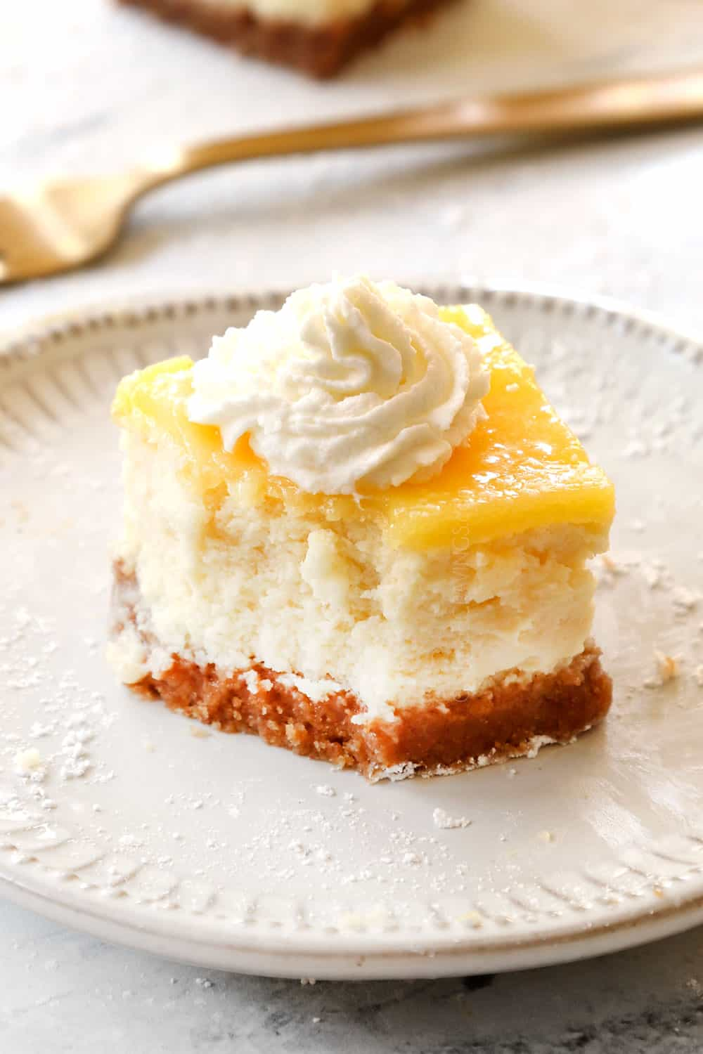 up close of lemon cheesecake bar with a bite out of showing how creamy it is