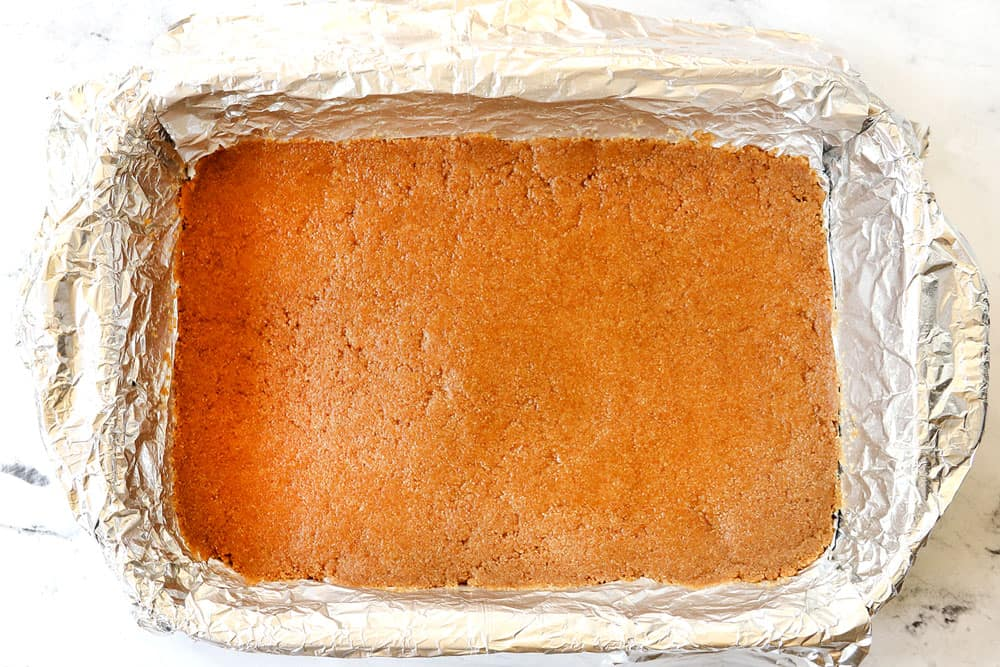 showing how to make lemon cheesecake bars by baking graham cracker crust in a 9x13 baking dish