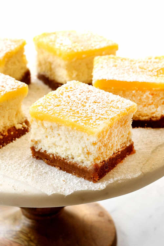 lemon cheesecake bars with lemon curd topping on a cake pedestal
