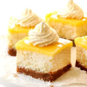 up close of lemon cheesecake bars with whipped cream on a cake pedestal