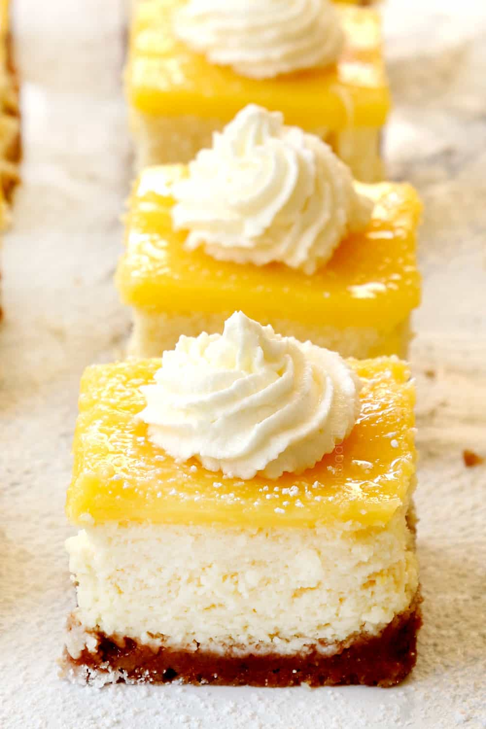 lemon cheesecake bars lined up on a marble counter