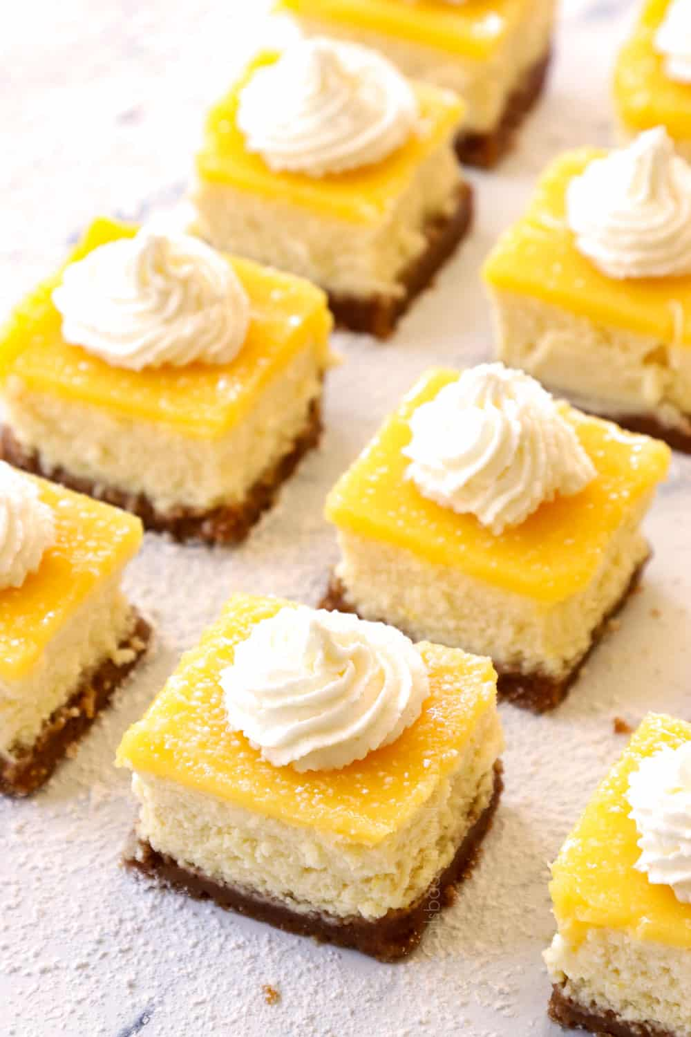 cheesecake bars with lemon curd topped with whipped cream