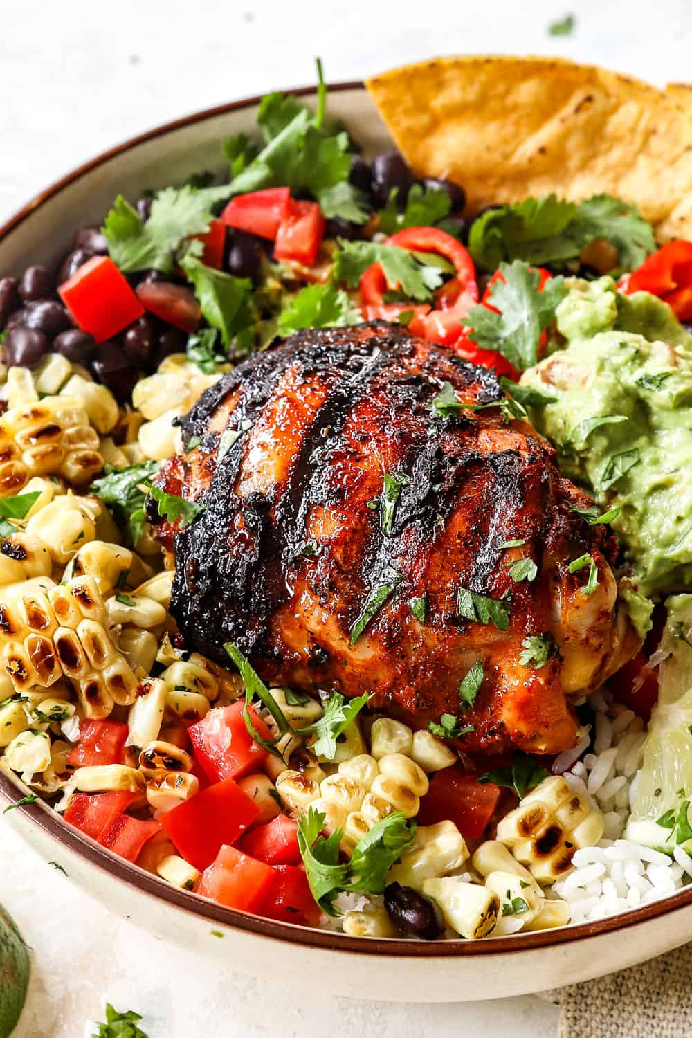 showing how to serve pollo asado with sides by adding to rice, corn, and salad