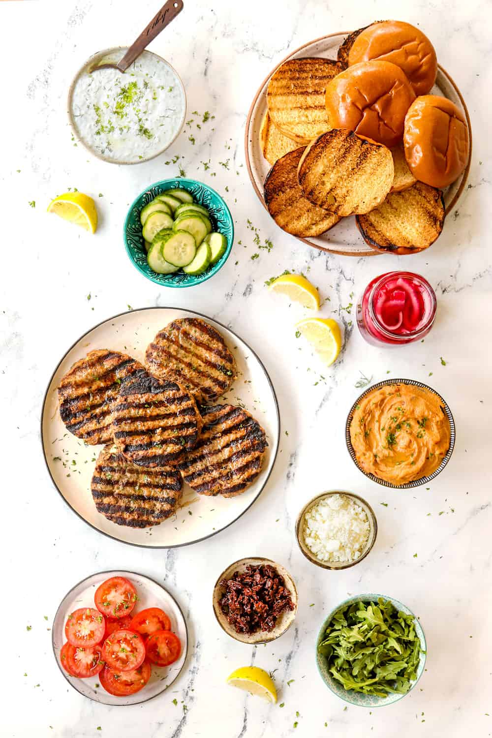 showing how to make Greek lamb burger recipe with top view of lamb burger patties and toppings: hummus, cucumbers, red onions, tomatoes, sun-dried tomatoes, tzatziki