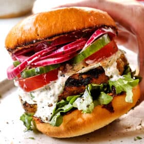 showing toppings for lamb burger Greek style by topping buns with arugula, lamb patties, tomatoes, cucumbers, tzatziki and red onions