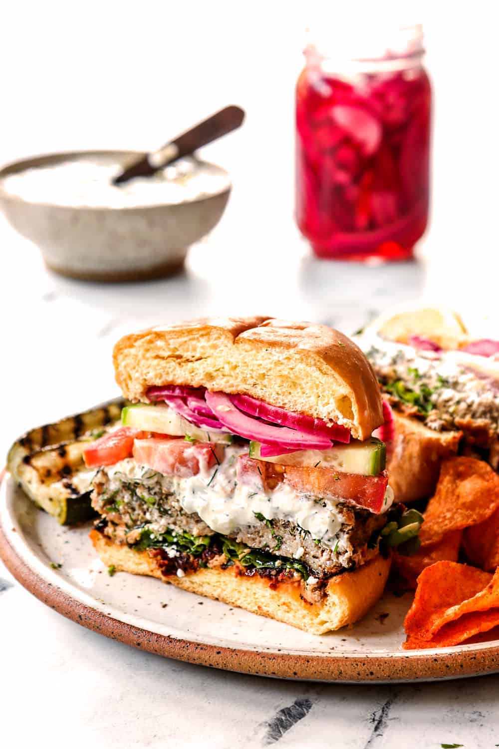 showing the inside of Greek burgers by cutting half to show lamb burger patty layered with tzatziki, cucumbers, tomatoes and red onions