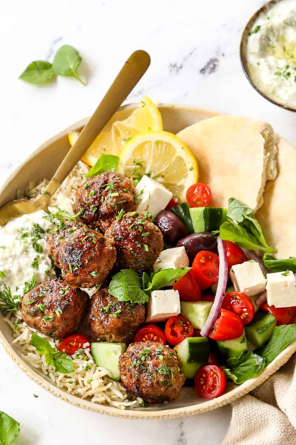 showing how to serve Greek Lamb (Keftedes) by adding to a plate with Greek salad and pitas