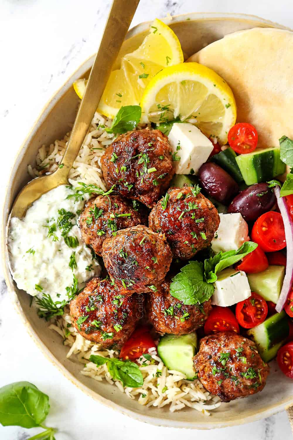 top view of Greek Meatball recipe (Keftedes) with lamb meatballs on a plate with tzatziki, rice, Greek salad and pita