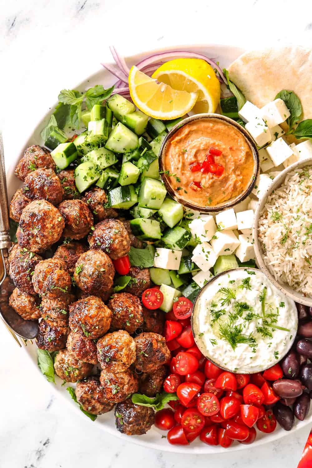 showing how to serve Greek Meatballs (Keftedes) with a top view of a meze platter with cucumbers, tomatoes, olives, feta, pitas, tzatziki and hummus