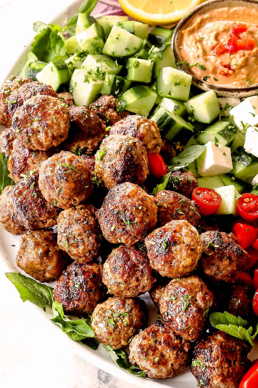 Greek Meatball recipe (Keftedes) with lamb meatballs on a platter with cucumbers and hummus
