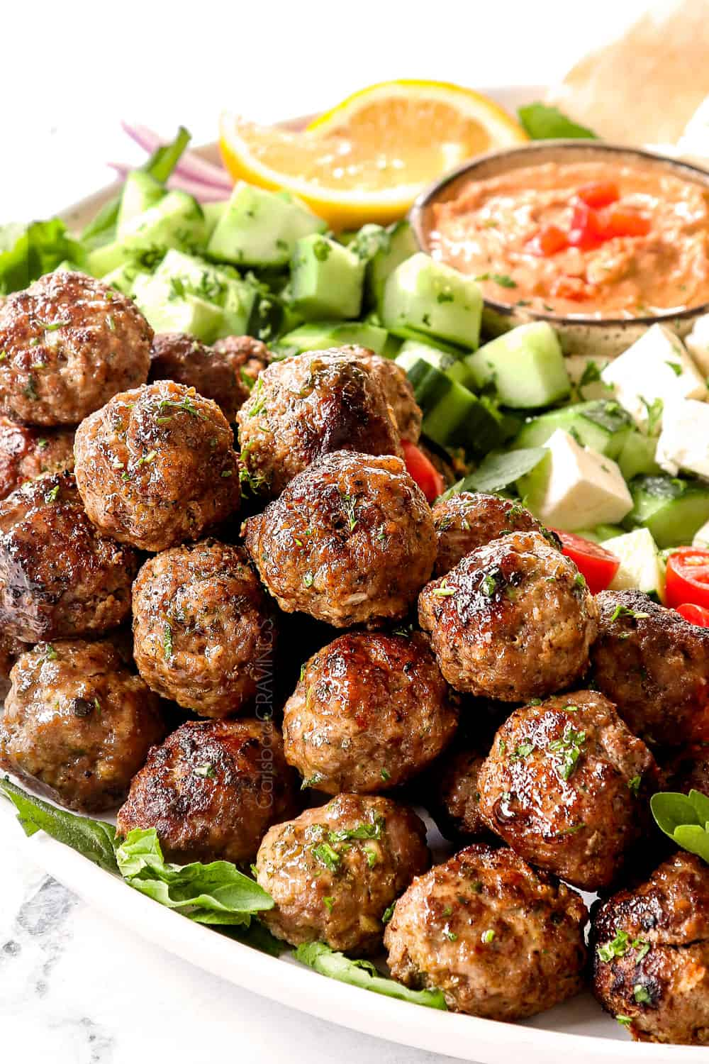 Greek Meatball recipe on a white platter with cucumbers and hummus showing how juicy they are