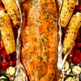 top view of grilled salmon in foil with grilled vegetables