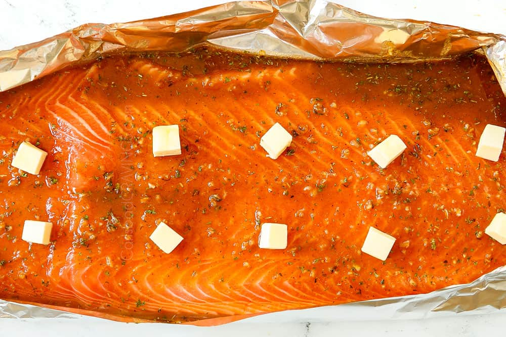 showing how to make grilled salmon in foil by adding butter to the top of the salmon