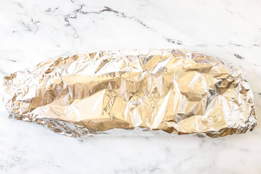 showing how to make grilled salmon in foil by sealing the salmon in foil