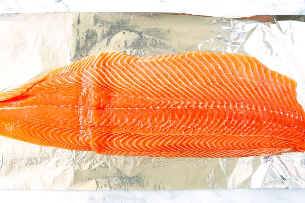 showing how to grill salmon in foil by adding salmon to heavy duty foil