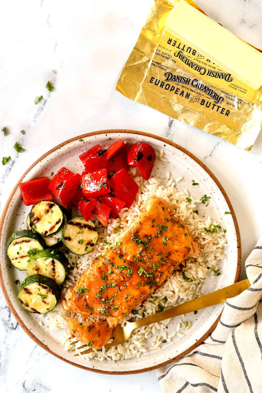 grilled salmon in foil on a plate with rice and vegetables
