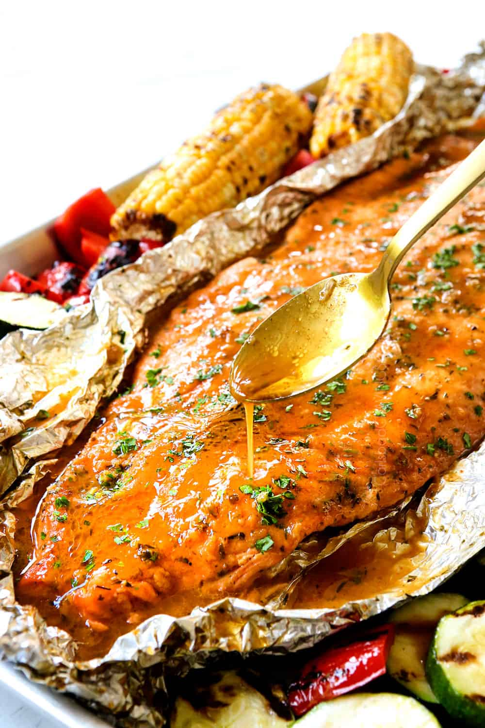 showing how to make grilled salmon in foil by drizzling salmon with butter