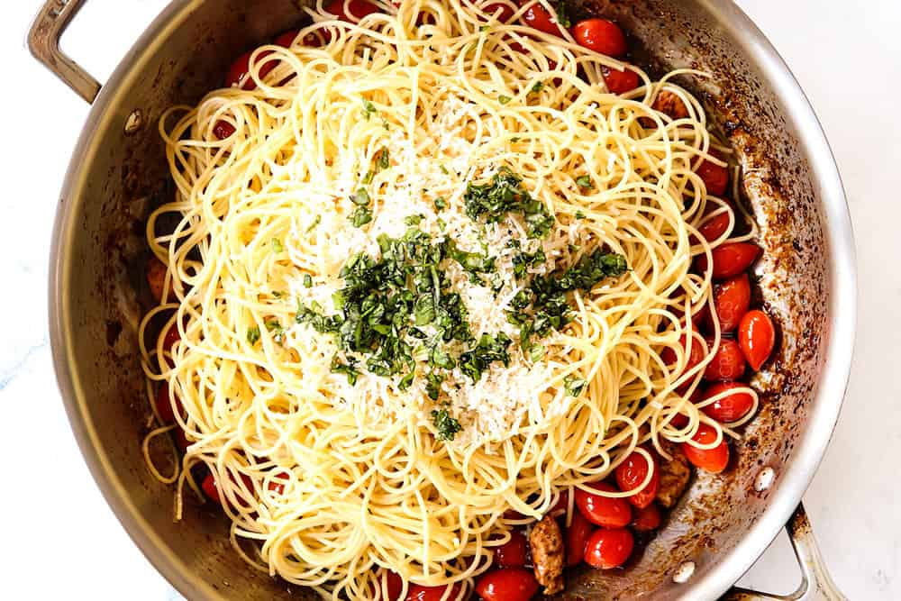 showing how to make bruschetta chicken pasta by adding pasta, parmesan and basil to the skillet with the chicken, tomatoes, garlic and sauce