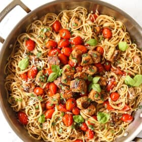 top view of bruschetta chicken pasta recipe with chicken, tomatoes and basil