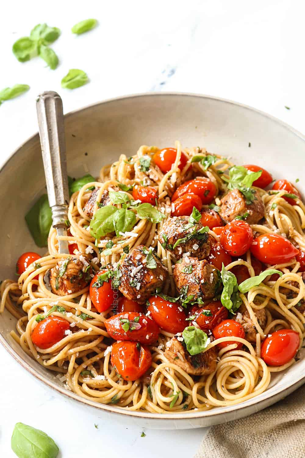 showing how to serve bruschetta chicken pasta recipe by adding to a bowl and garnishing with Parmesan and fresh basil