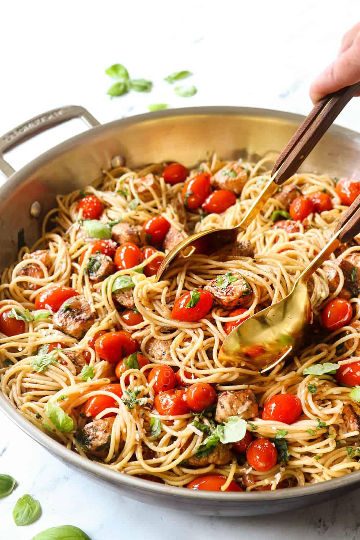 serving bruschetta chicken pasta recipe with tongs
