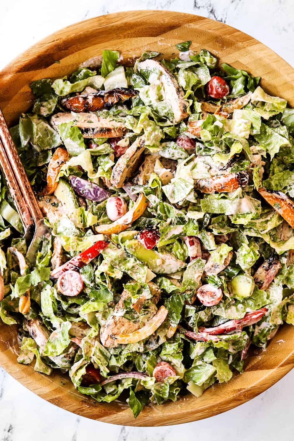showing how to make chicken fajita salad by tossing with creamy dressing