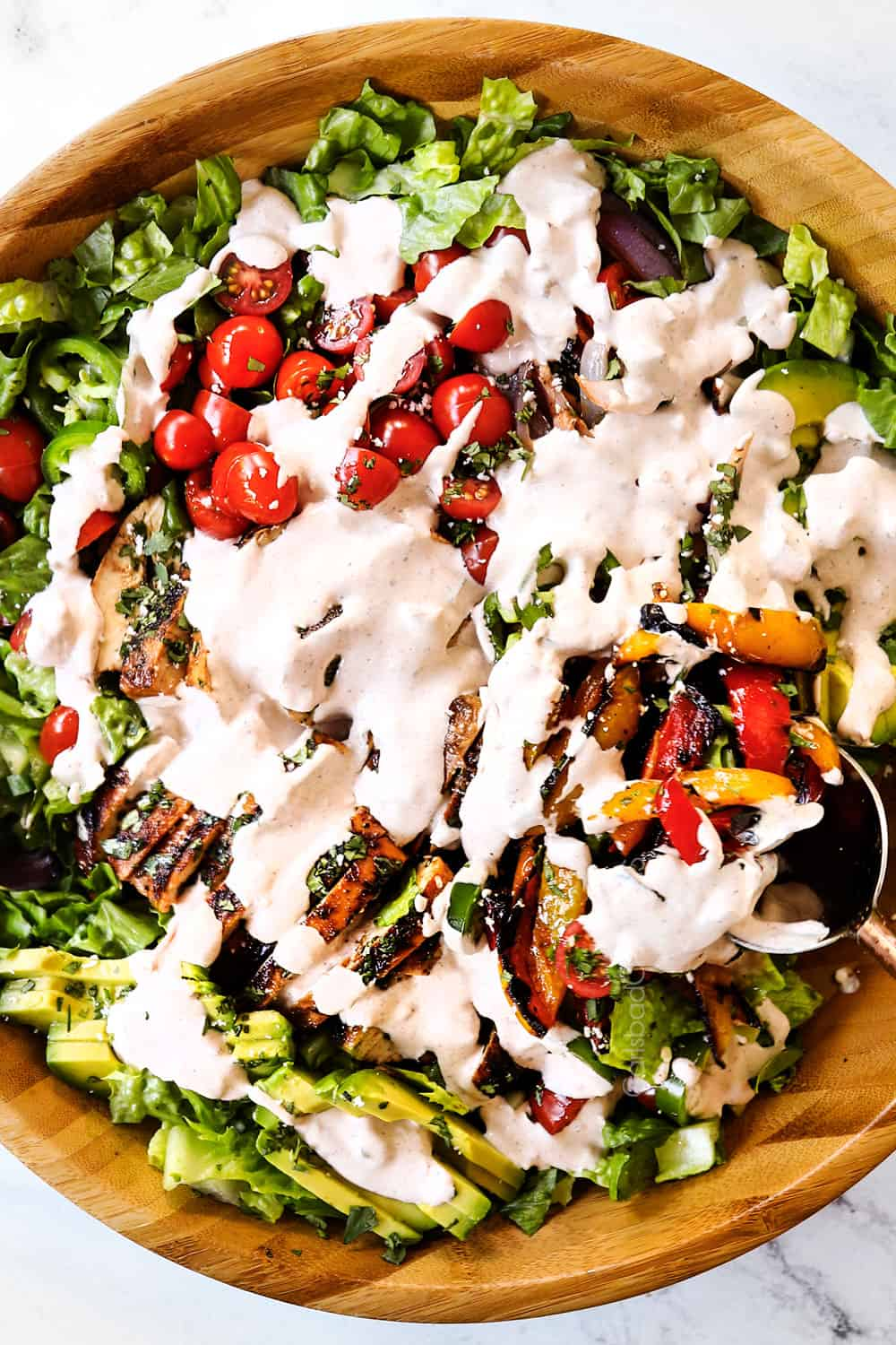 showing how to make chicken fajita salad by drizzling with creamy dressing