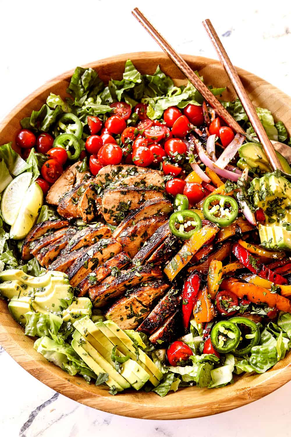 chicken fajita salad (chicken salad recipe) with chicken, bell peppers, red onions, tomatoes, avocados, cilantro in a wood bowl