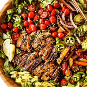top view of chicken fajita salad (chicken salad recipe) in a wood bowl with chicken, tomatoes, avocados, bell peppers