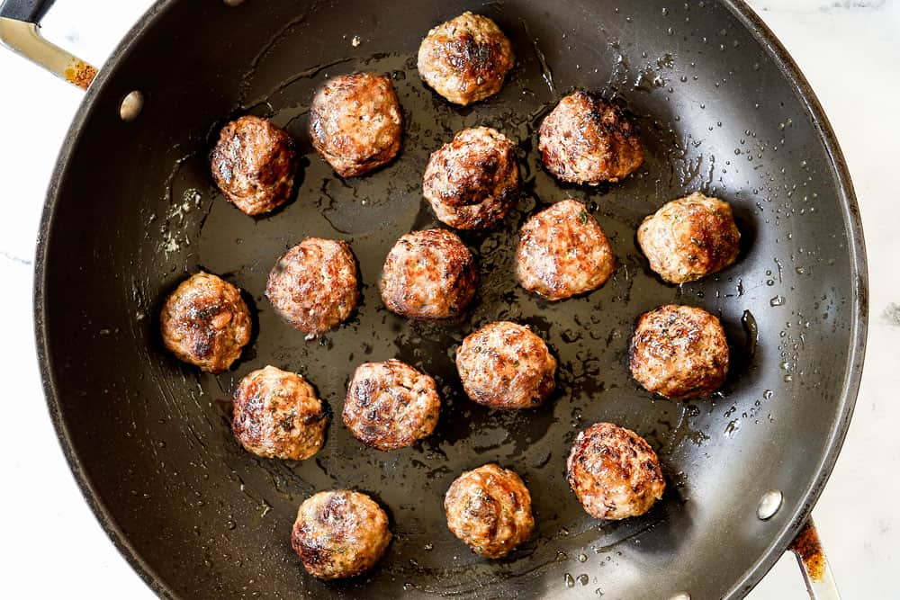 showing how to make Greek Lamb Meatball recipe (Keftedes) by pan frying meatballs in a black nonstick skillet