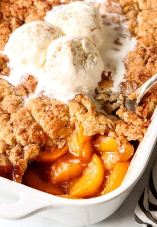 up close of scooping easy peach cobbler with fresh peaches