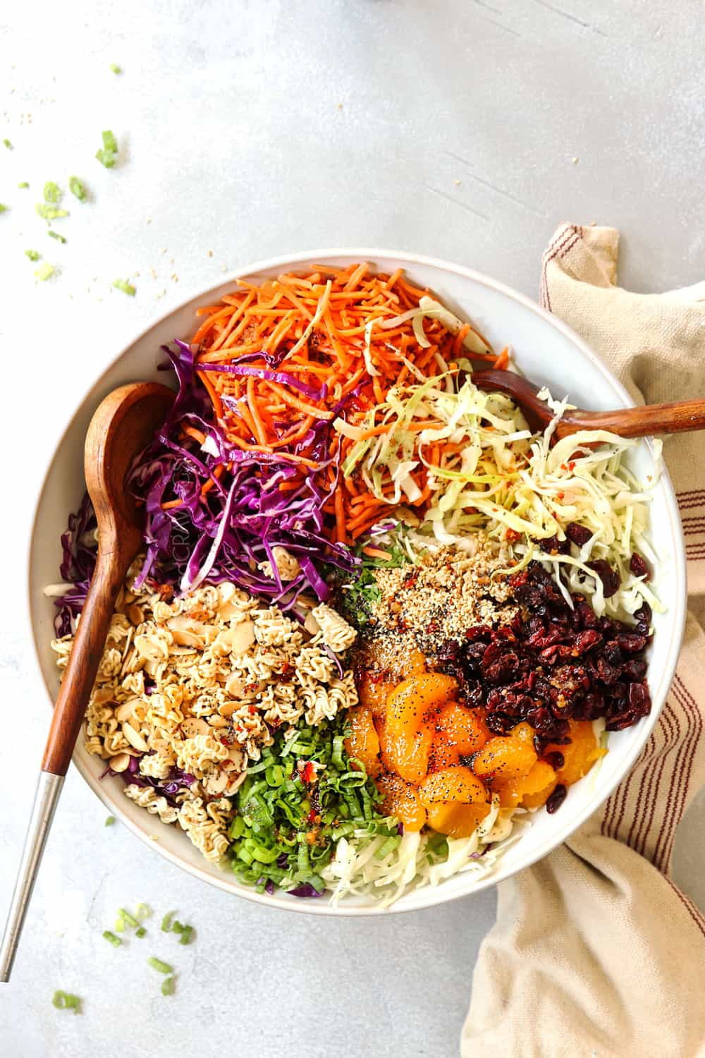 showing how to make Ramen Noodle Salad recipe by adding toasted ramen, cabbage, carrots and sesame seeds to a large white bowl