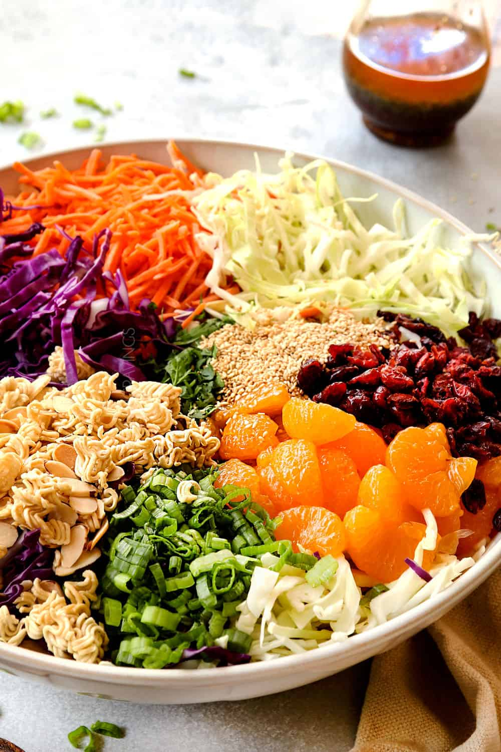 showing how to make Ramen Noodle Salad recipe with side view of ingredients in a bowl: cabbage, carrots, ramen noodles, almonds and optional toppings of sunflower seeds, Mandarin oranges, green onions and dried cranberries