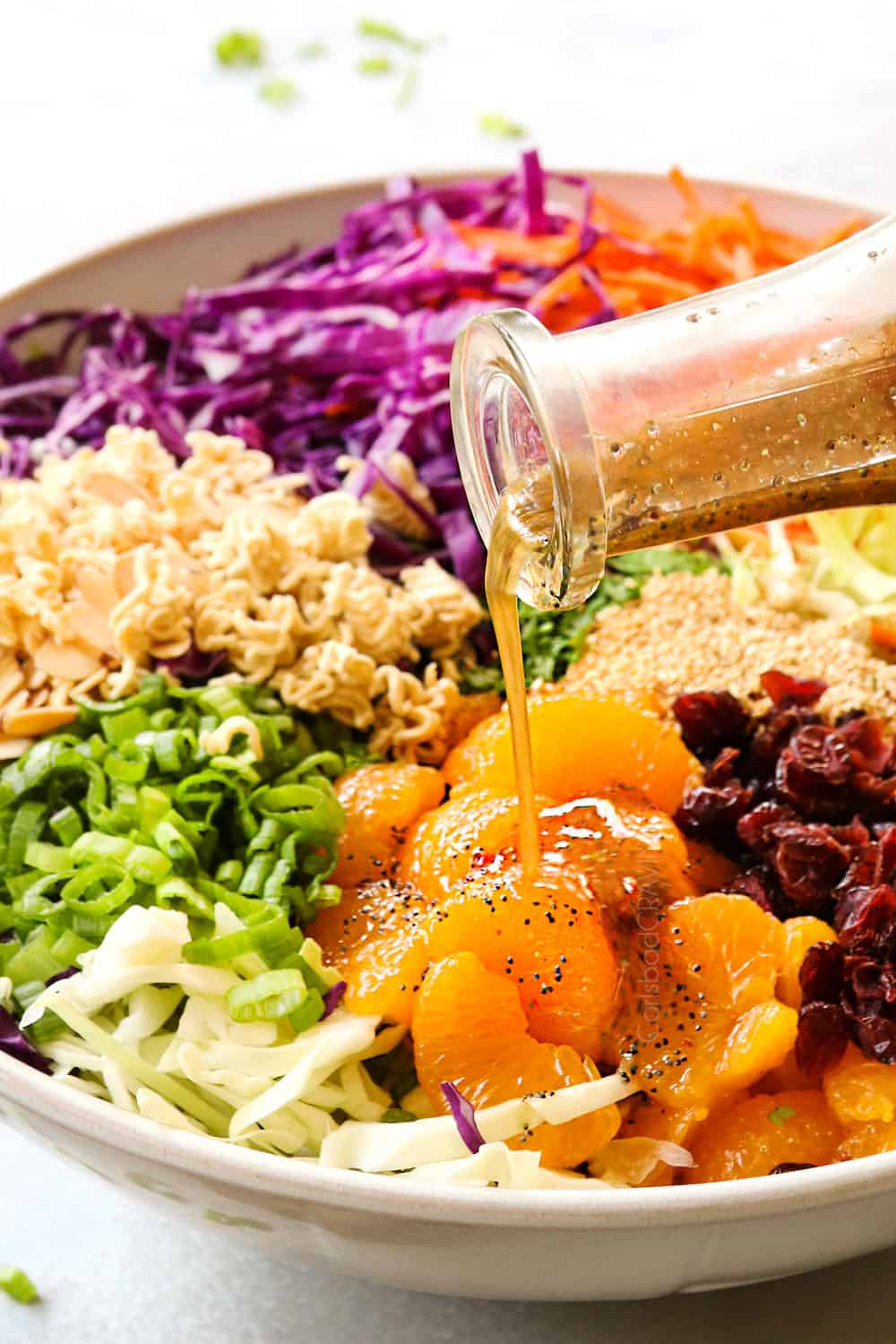 showing how to make Ramen Noodle Salad recipe by pouring salad dressing over the salad
