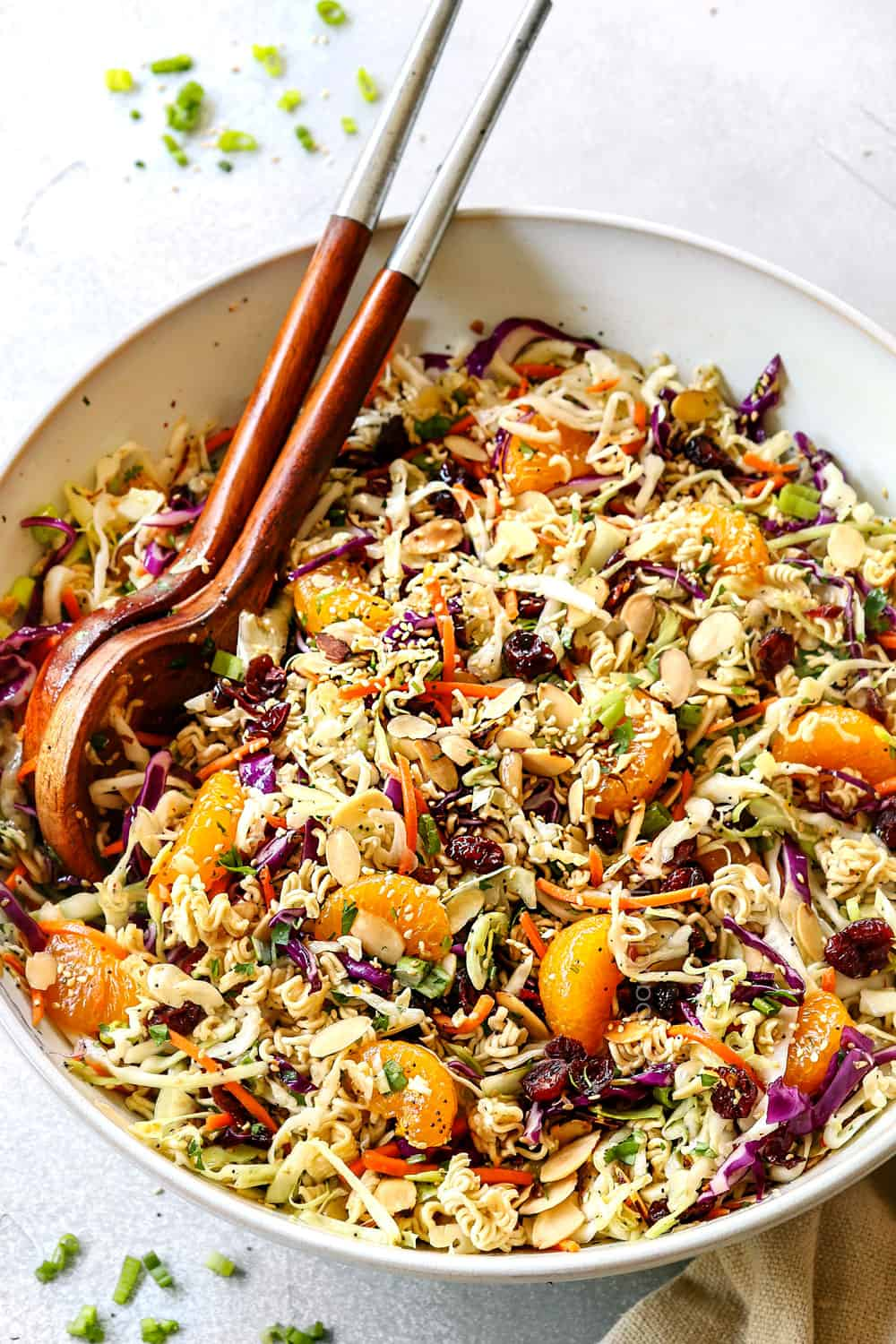 showing how to make Asian Ramen Noodle Salad by tossing the salad with the dressing in a white bowl