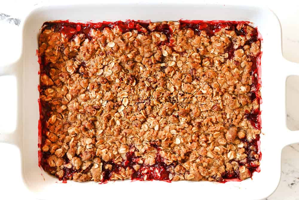 showing how to make strawberry crisp (crumble) by baking until the topping is golden and crispy