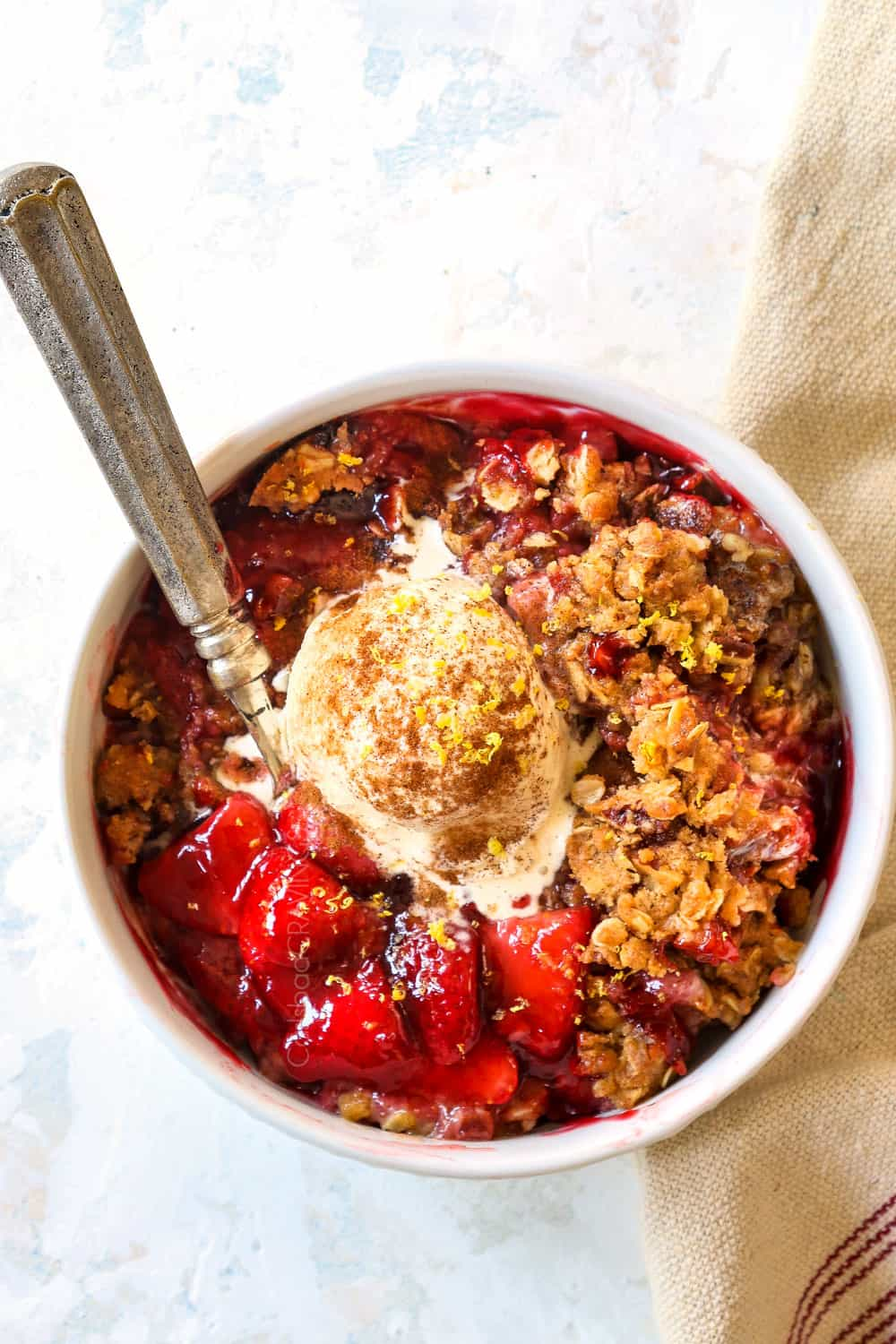 top view of strawberry crisp recipe in a white bowl with oats