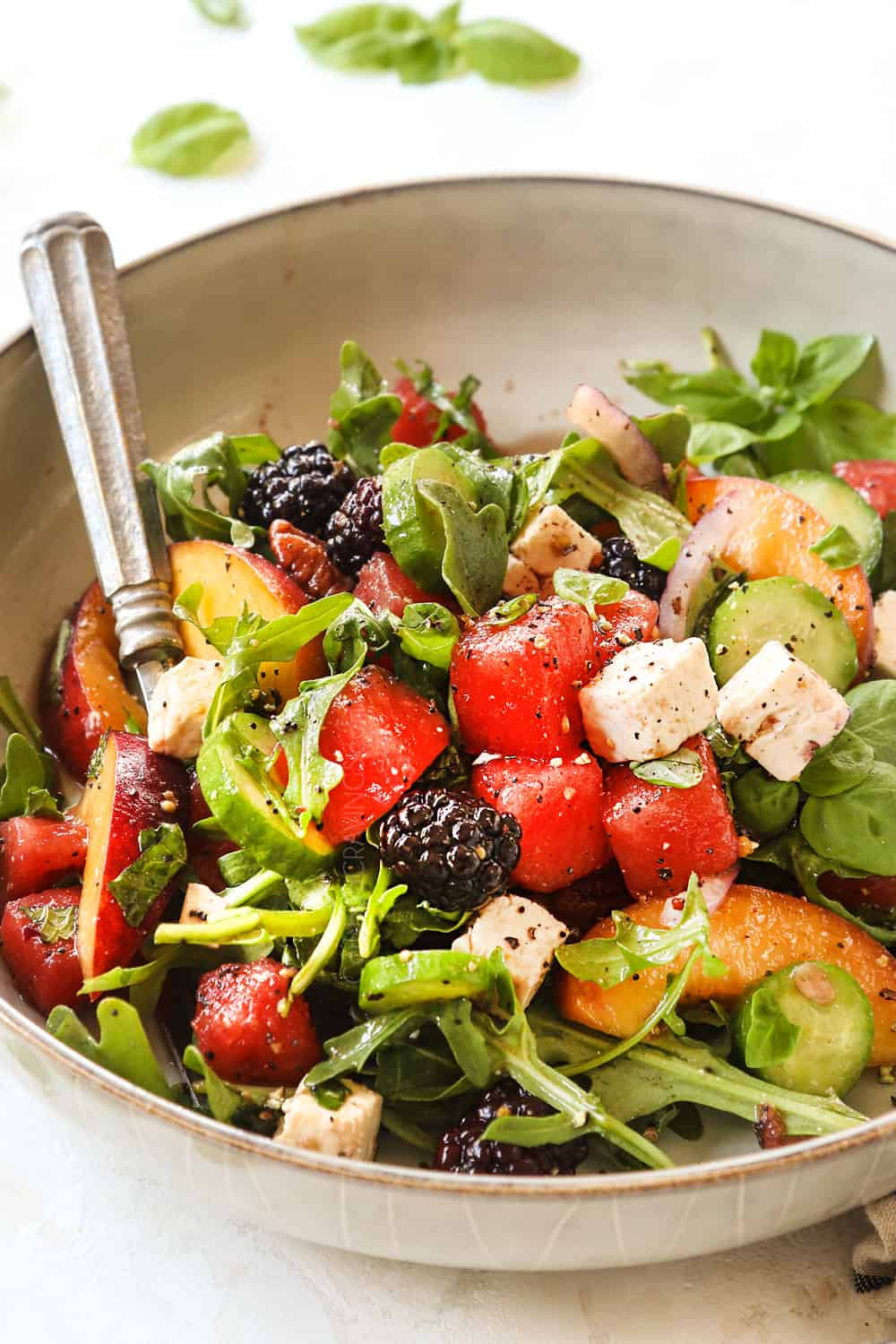 a bowl of watermelon salad with feta, mint, basil, cucumbers, and berries over a bed of arugula