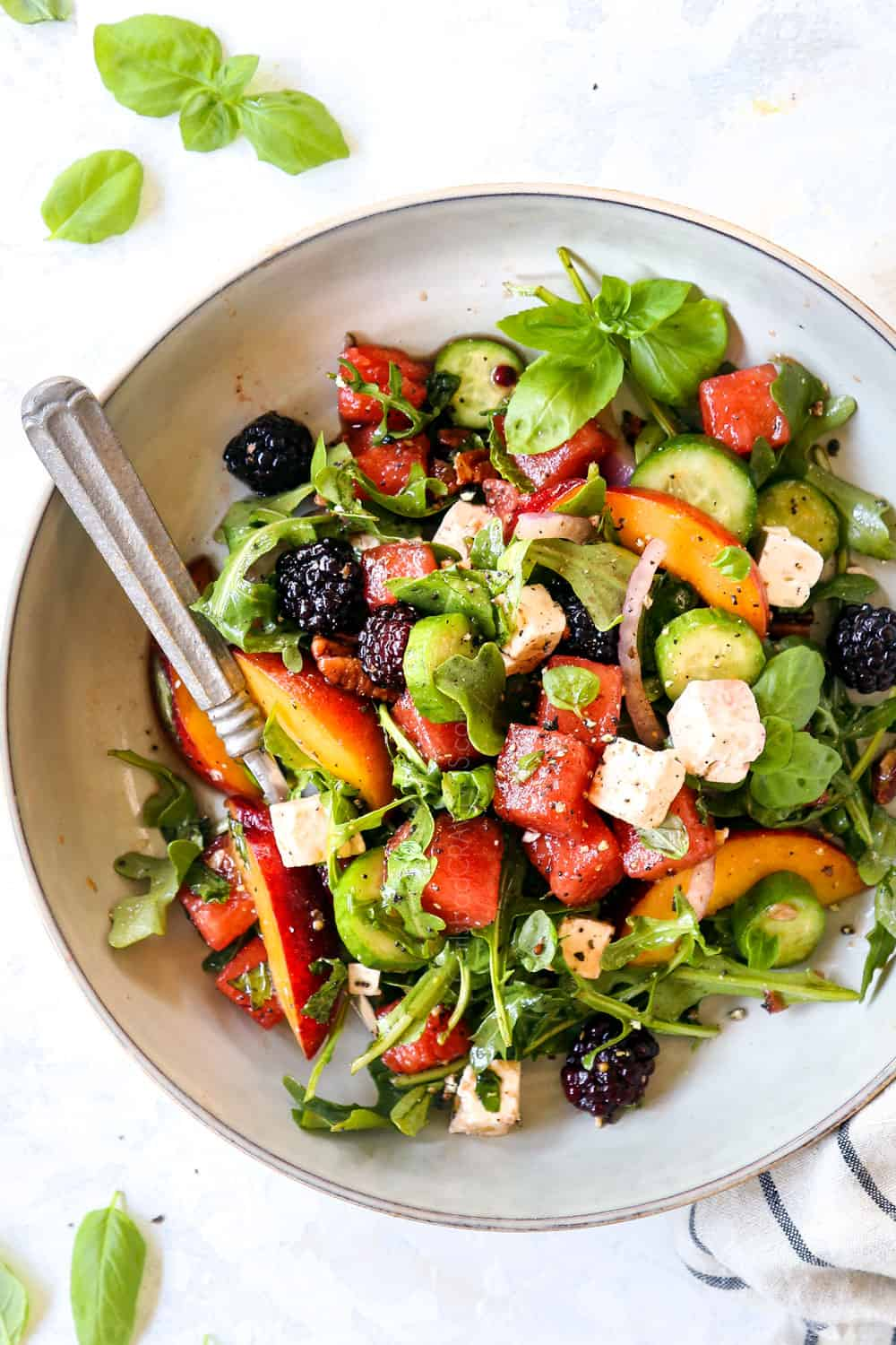 top view of watermelon feta salad with basil, cucumbers and arugula