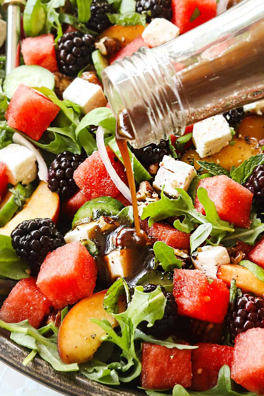 showing how to make watermelon salad recipe by drizzling with balsamic dressing